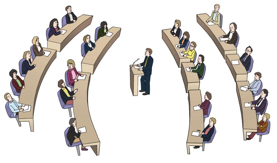 Blick von der Seite: In der Mitte das Redepult mit Blick nach links. Links zwei Reihen mit Menschen an Tischen. Rechts zwei Reihe mit Menschen an Tischen.