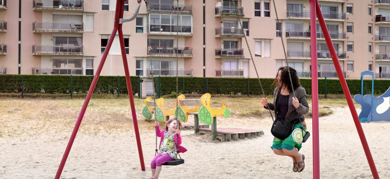 Plattenbau mit Schaukel, Kind und Frau
