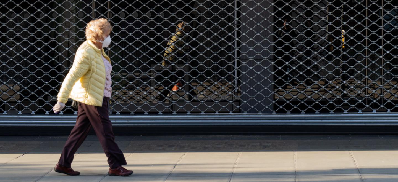 Corona Lockdown, Frau vor geschlossenen Geschäften