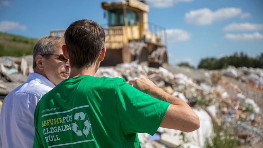 Benjamin Raschke steht mit einer weiteren Menschen vor einer illegalen Müllhalde in Brandenburg. © ideengruen.de/Markus Pichlmaier