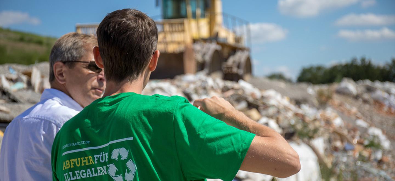 Benjamin Raschke steht mit einer weiteren Menschen vor einer illegalen Müllhalde in Brandenburg. © www.ideengruen.de | markus pichlmaier