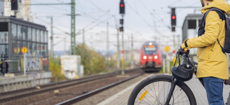 Mensch wartet mit Fahrrad auf den Zug