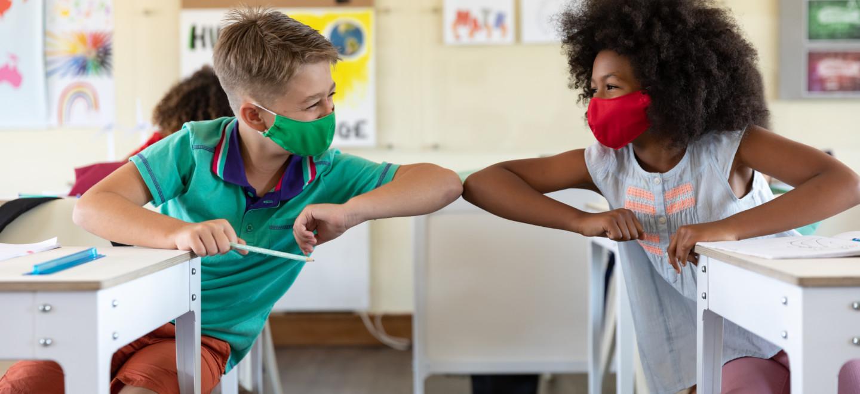 Zwei Kinder in der Schule mit Masken